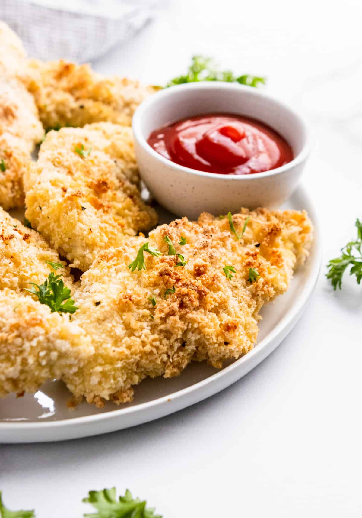 Cornmeal baked breaded chicken tenders on white plate with ketchup.
