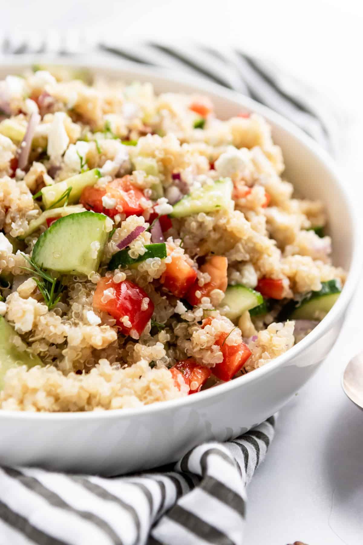 Bowl of salad with quinoa, cucumber, feta and pepper.