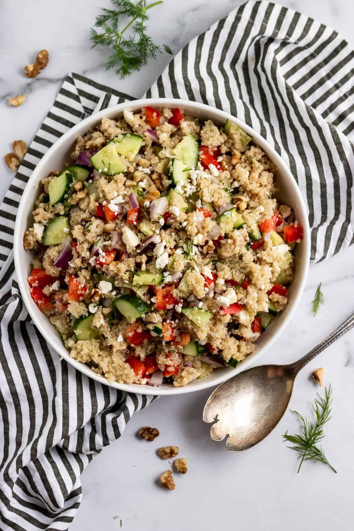 Feta quinoa salad in bowl with serving spoon.