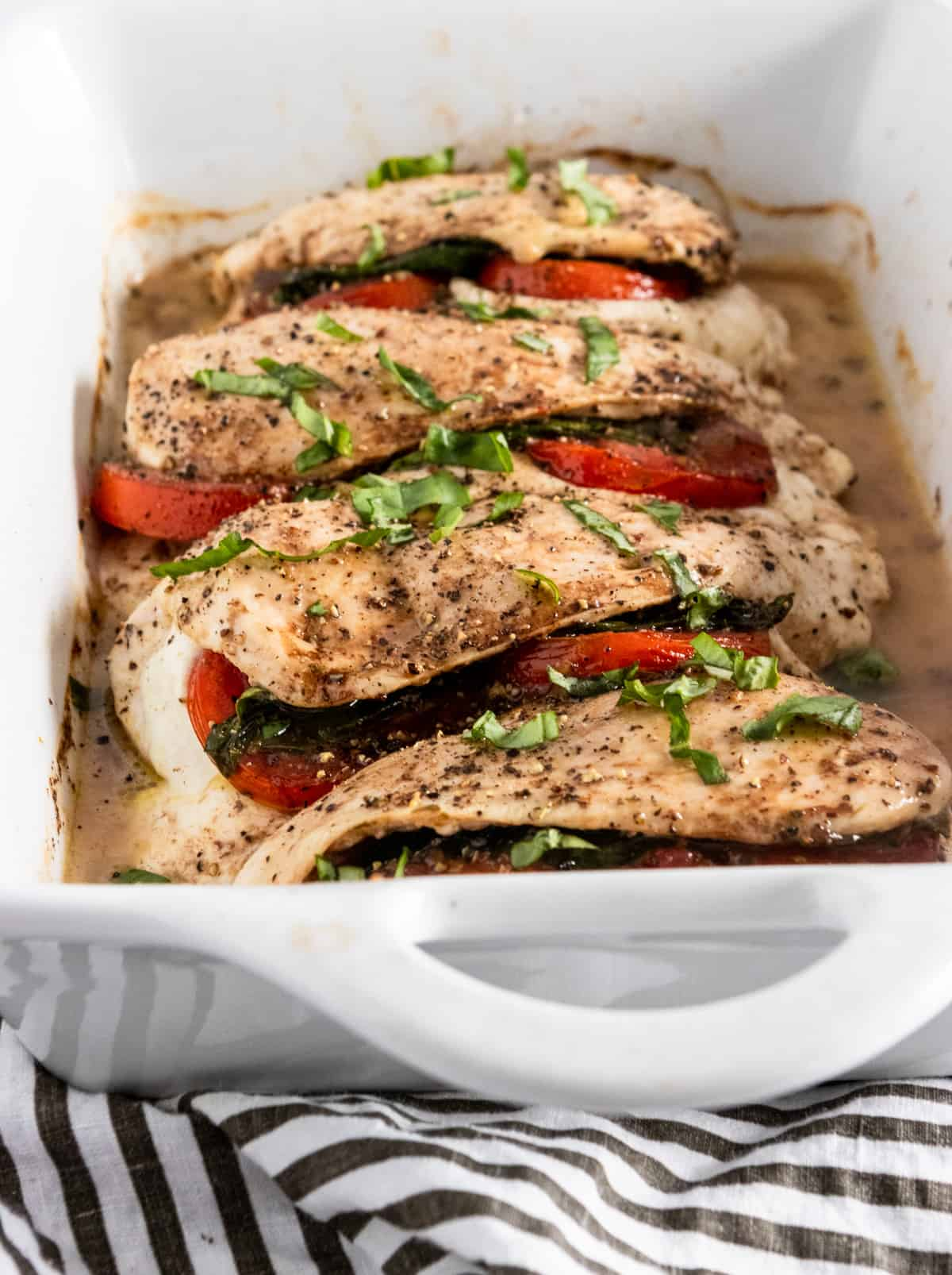 Chicken breast in baking pan with tomato and mozzarella.