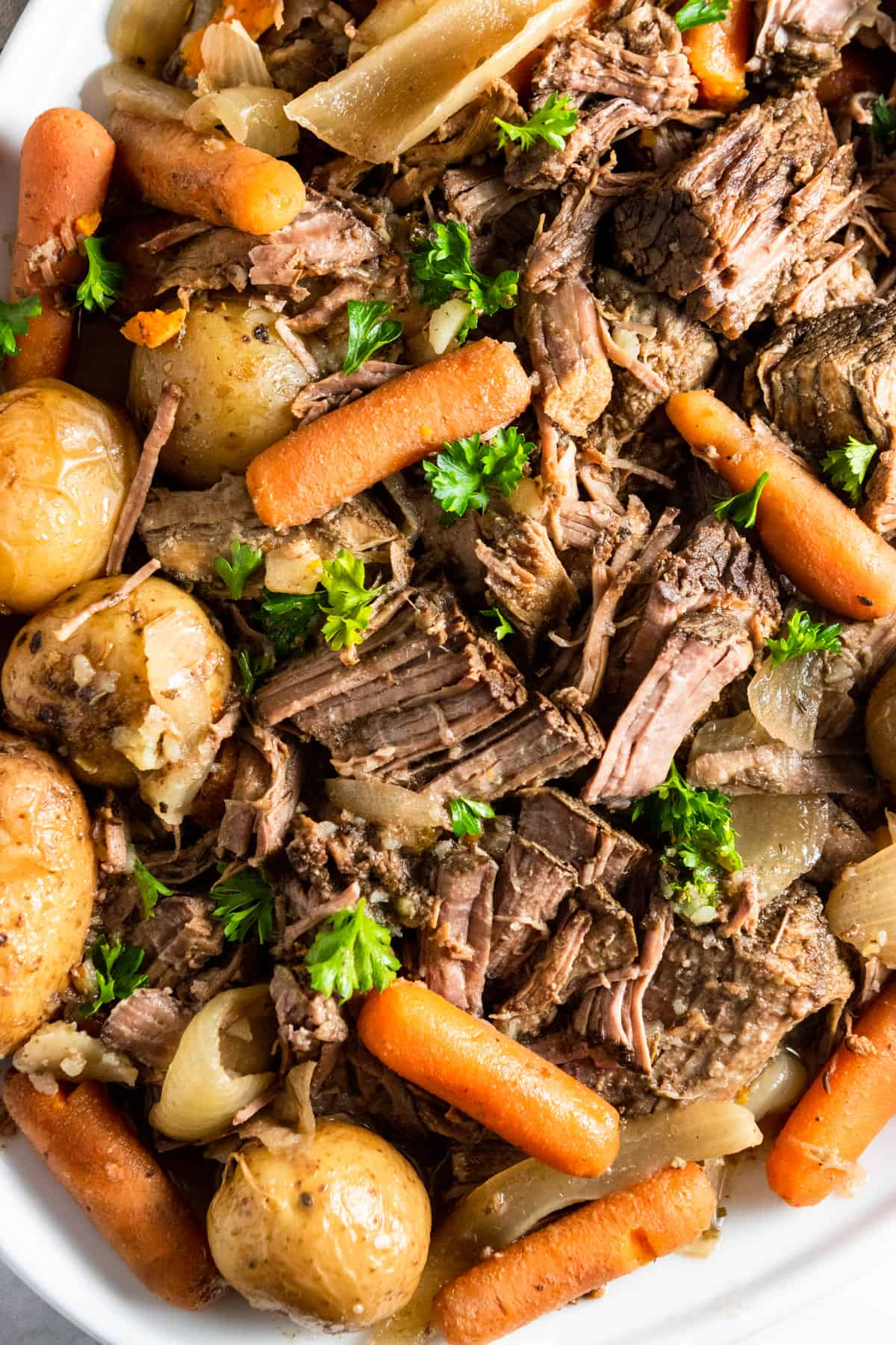 Overhead shot of cooked slow cooker pot roast on white plate.