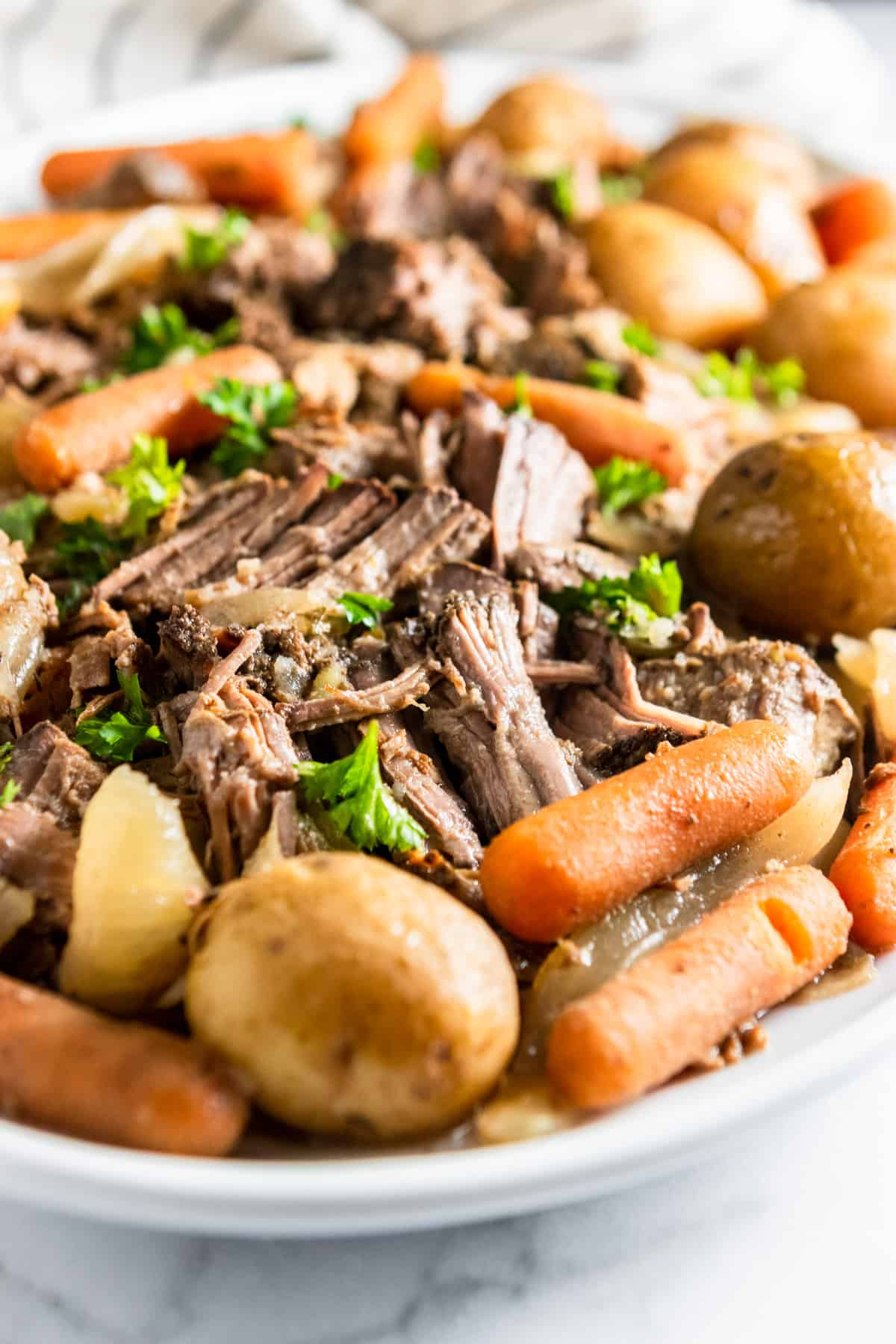 Slow Cooker Pot Roast with carrots, potatoes and onions on serving platter.