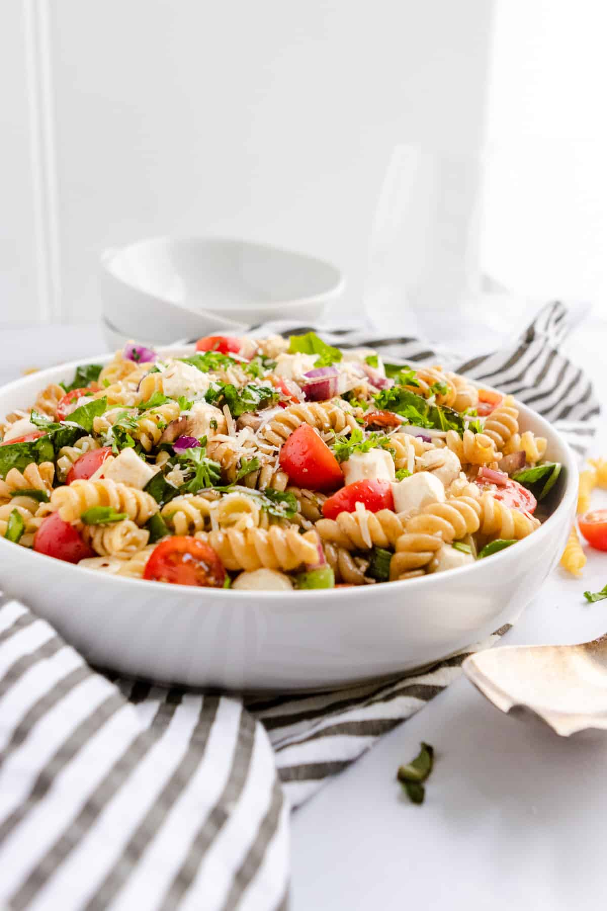 Pasta salad in white bowl with serving bowls.