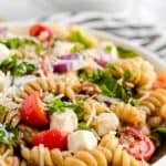 Bowl of rotini pasta salad with fresh cherry tomatoes, basil and mozzarella.