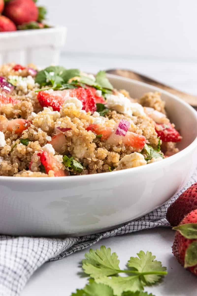 Quinoa salad in white serving bowl with napkin.