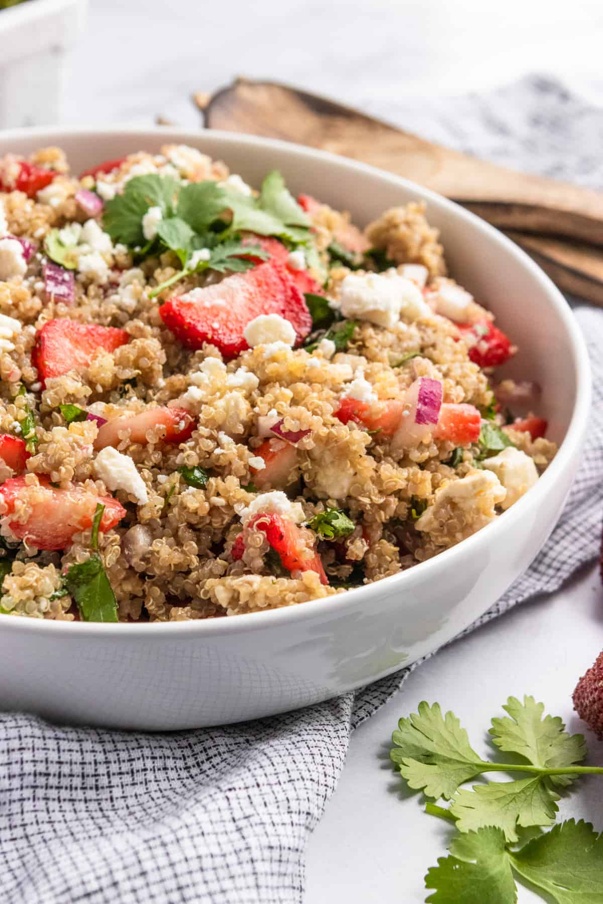 Strawberry summer quinoa salad in white bowl with serving utensils.