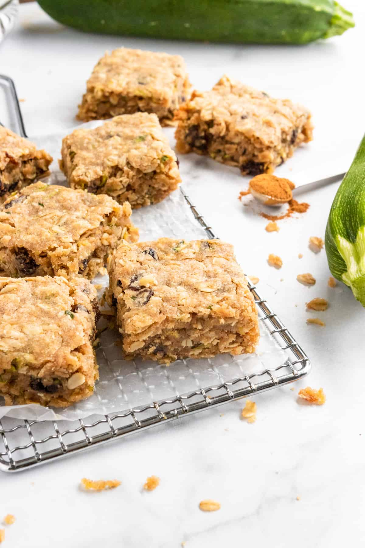 Zucchini bars on cooling rack with crumbs.