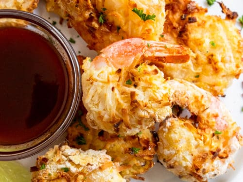 Coconut shrimp on white plate with sauce.