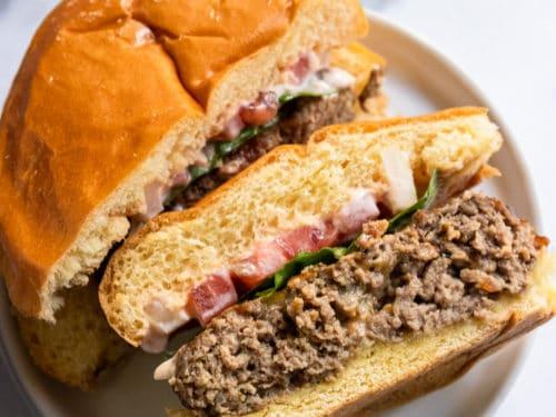 Air fryer hamburger on bun and white plate.