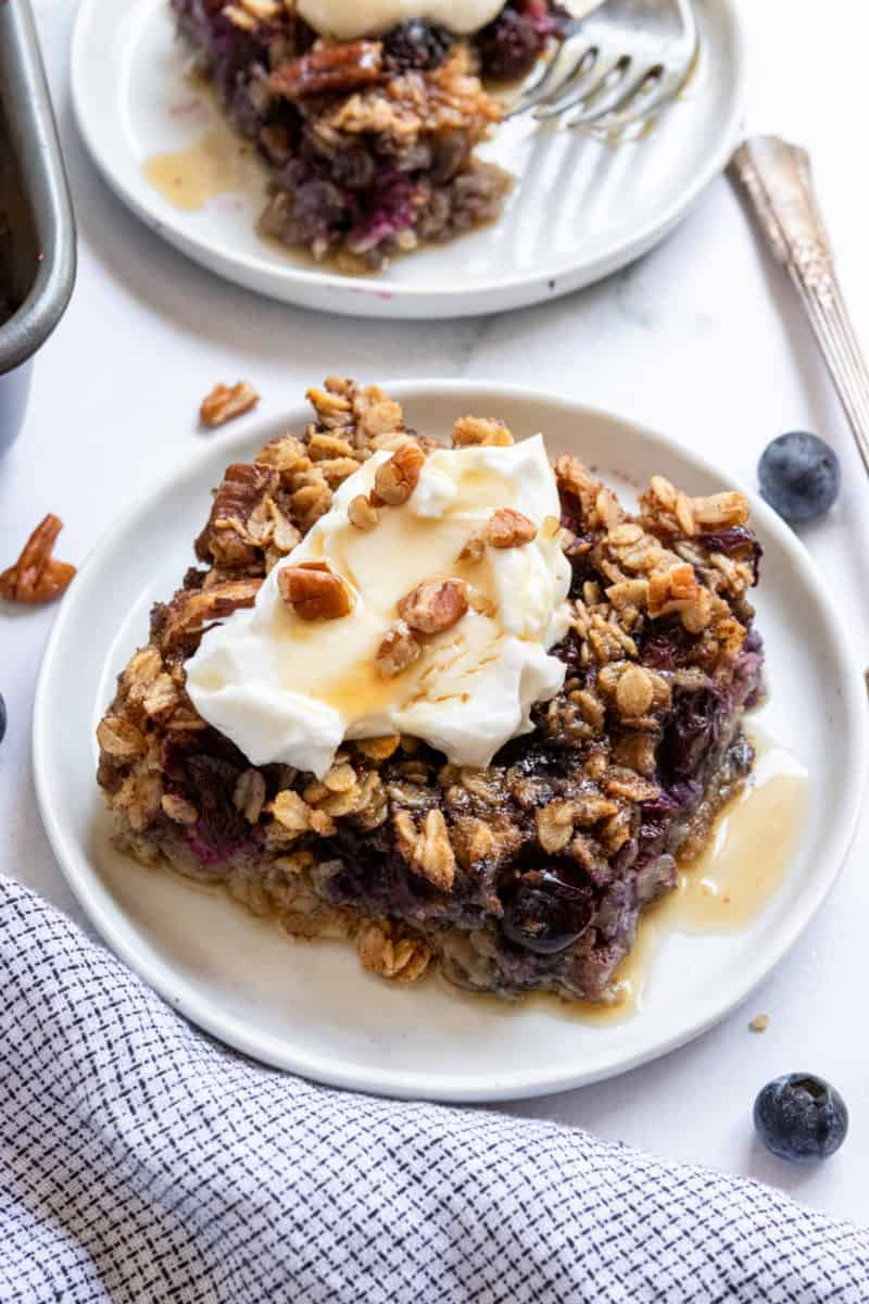 Slice of blueberry baked oatmeal on white plate with maple syrup.