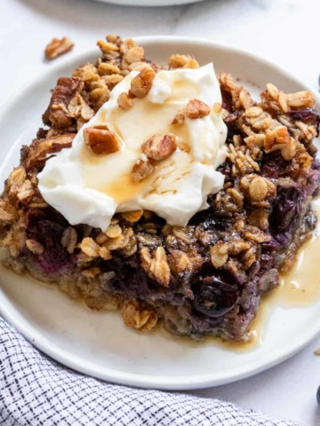 Blueberry oatmeal baked on plate with yogurt and maple syrup.