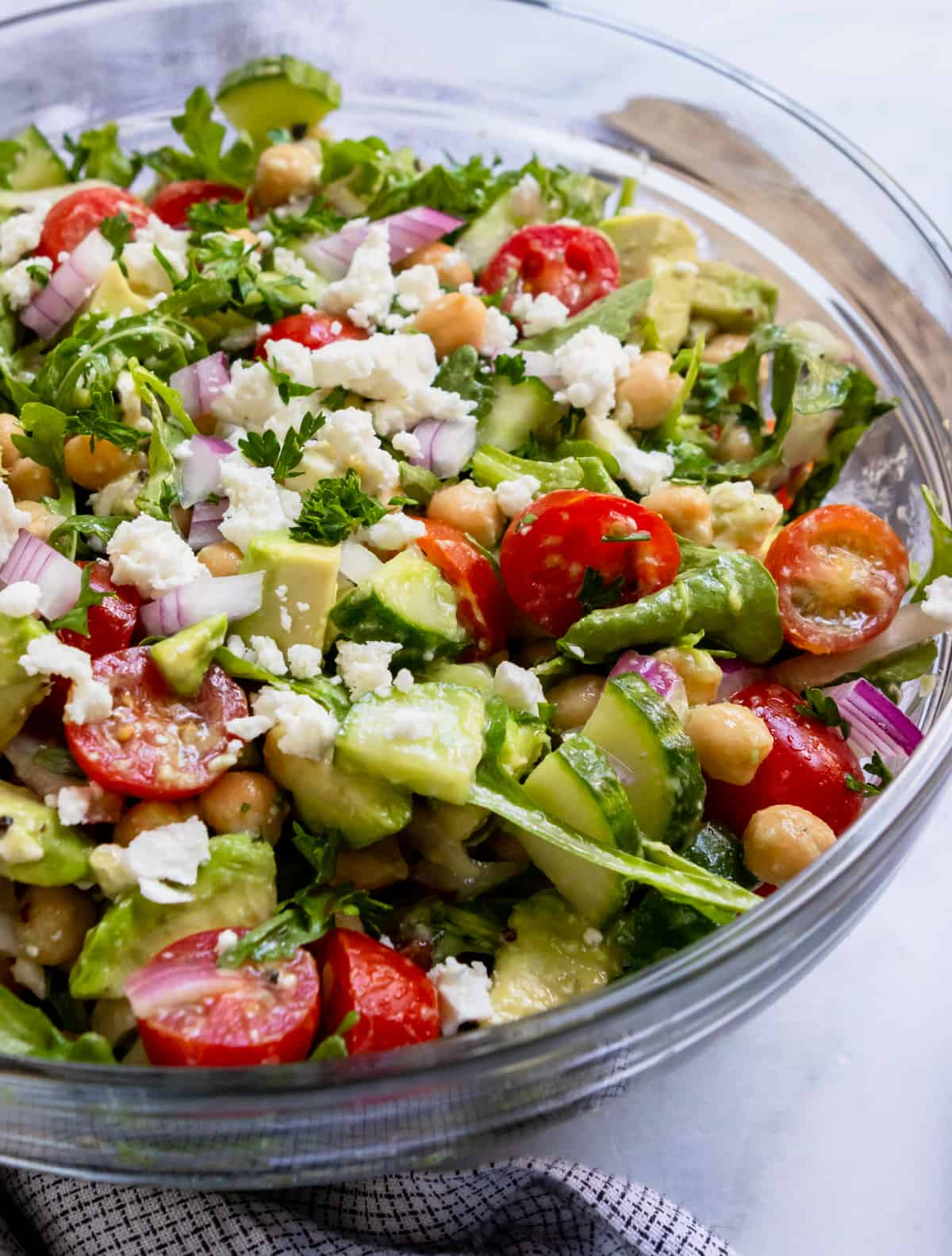 Chickpea avocado salad in clear bowl with fresh parsley.