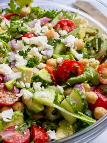 Chickpea salad with avocado, tomatoes and feta in glass bowl.