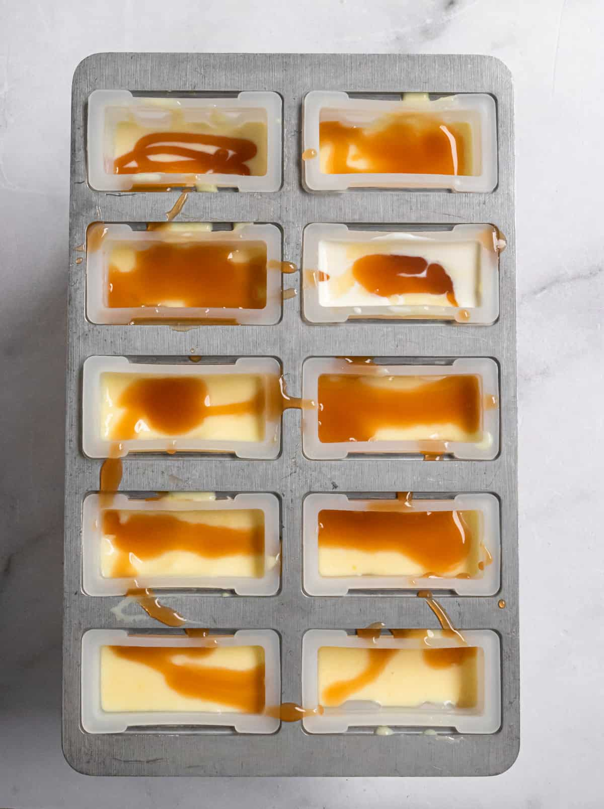 Popsicle molds filled with mixture and caramel.