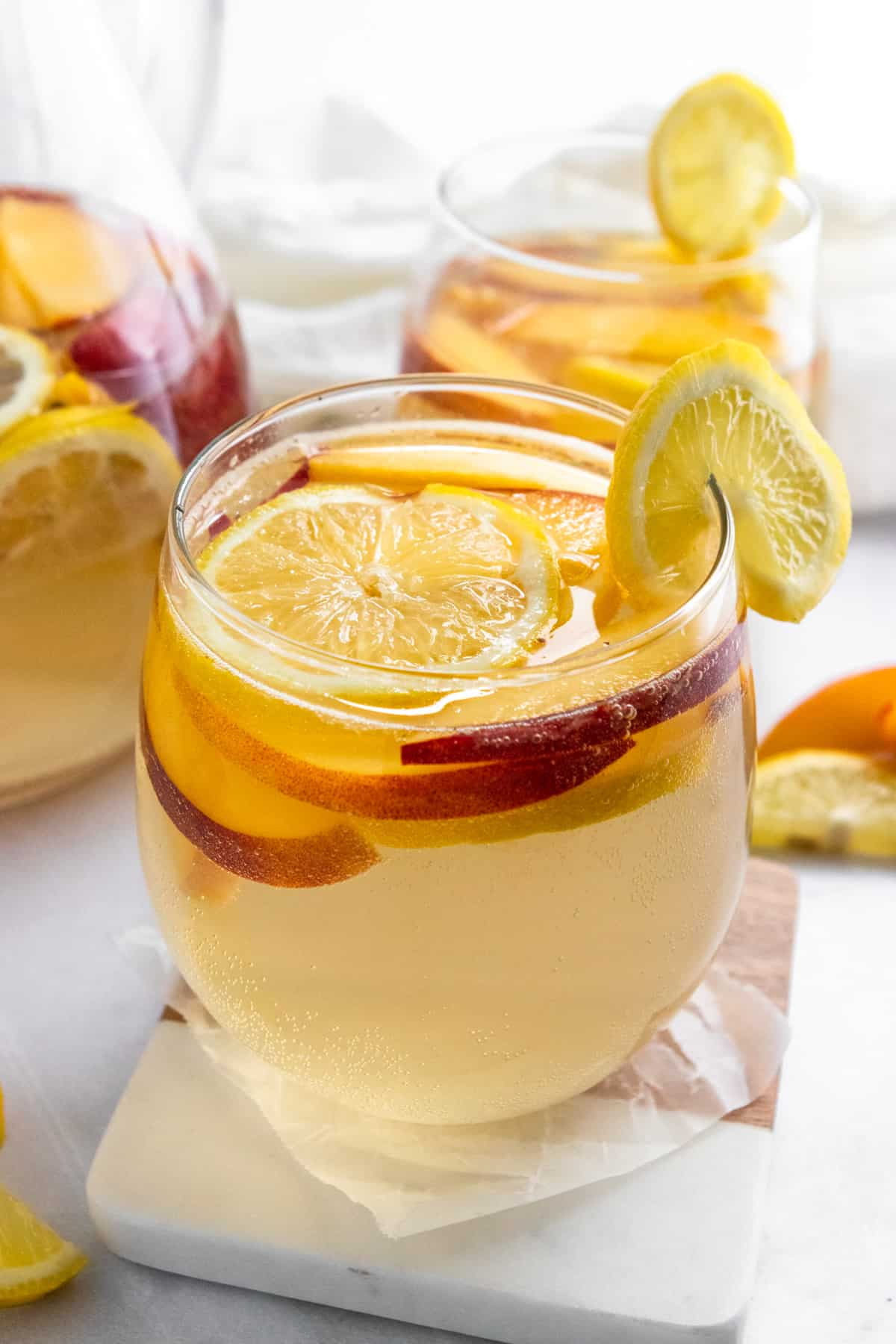 Ginger peach white sangria in glass with lemon slice on coaster.