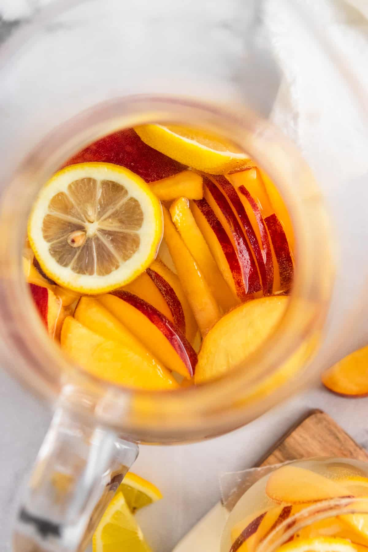 Overhead view of pitcher of peach white sangria.