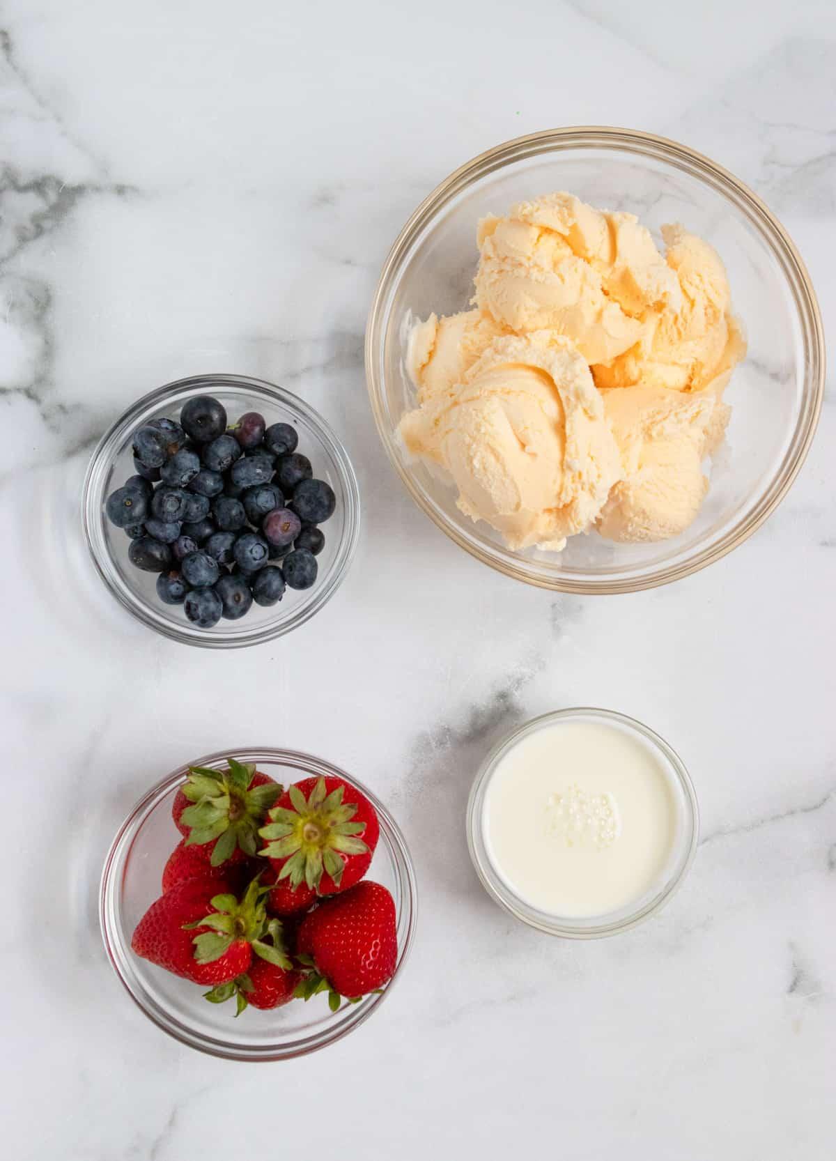 vanilla ice cream, milk and berries on counter.