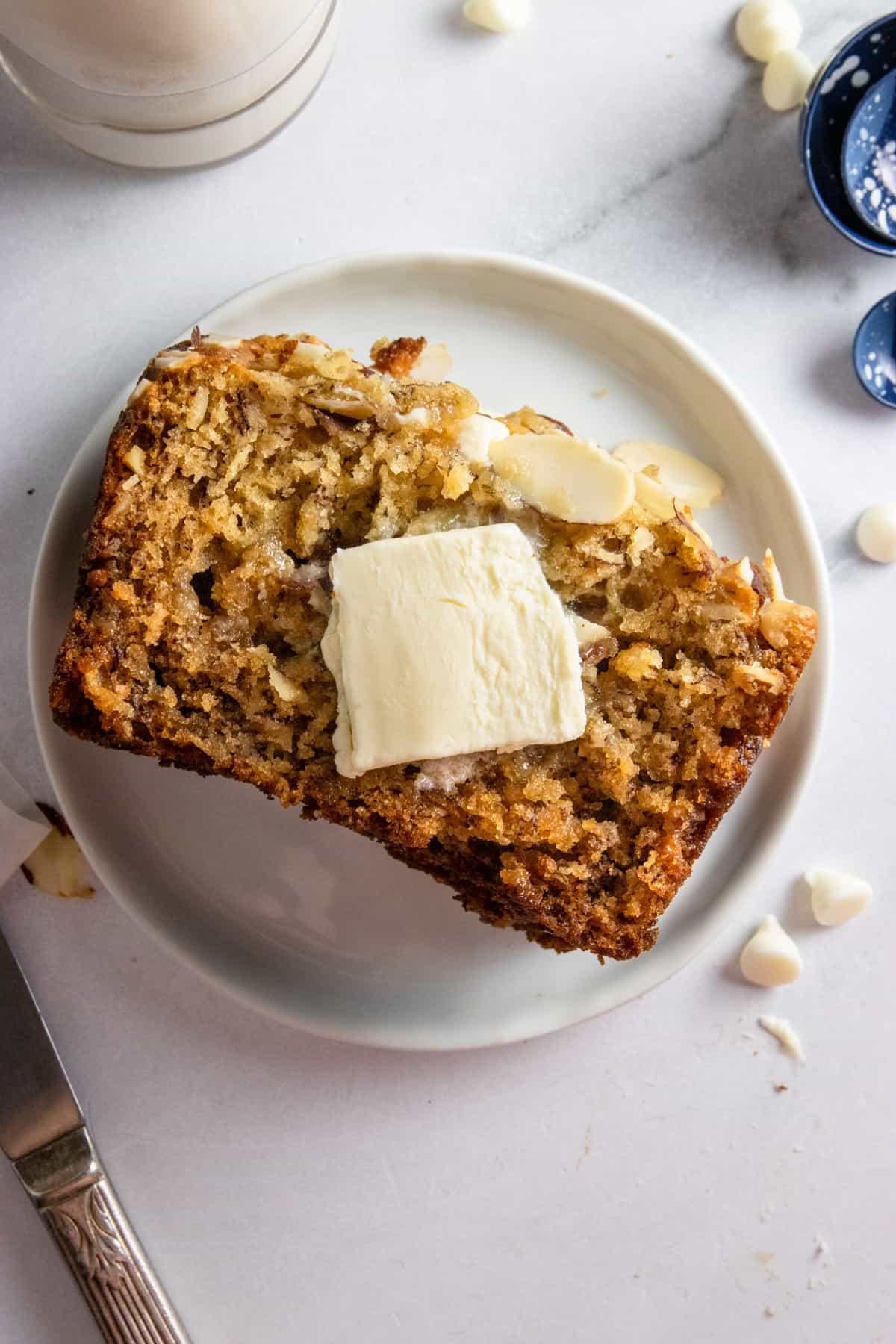 Banana bread made with ripe bananas on plate with butter.