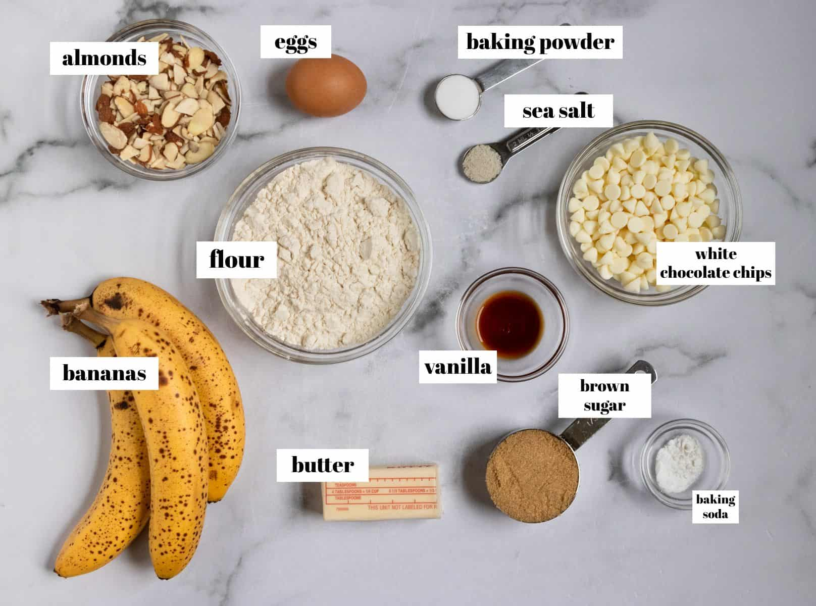 Ingredients needed to make banana bread on white counter.