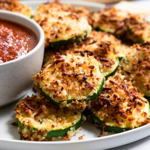 Zucchini with crispy cheese coating on plate.