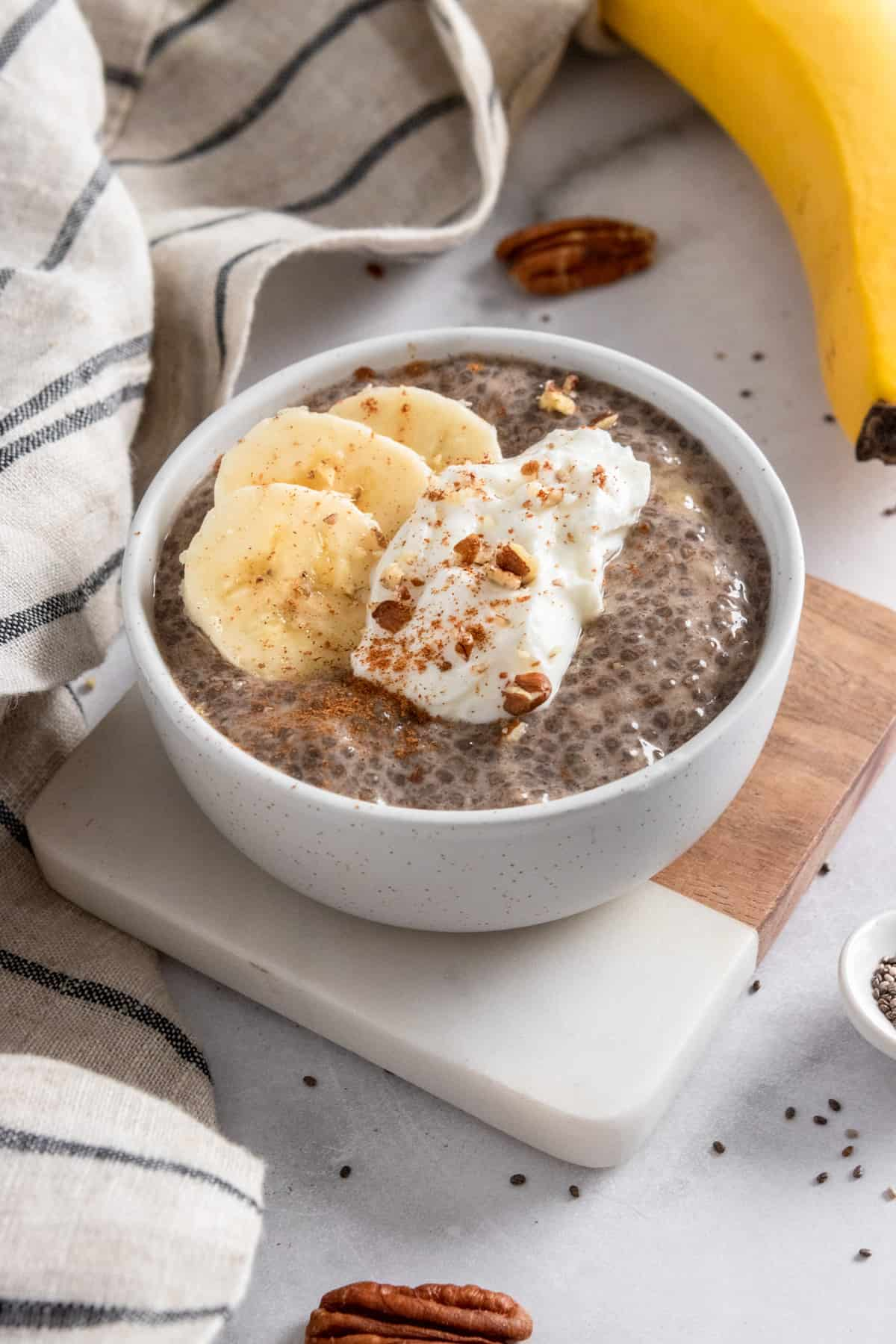 Banana chia seed pudding in bowl with dollop of yogurt, banana slices and cinnamon on top.