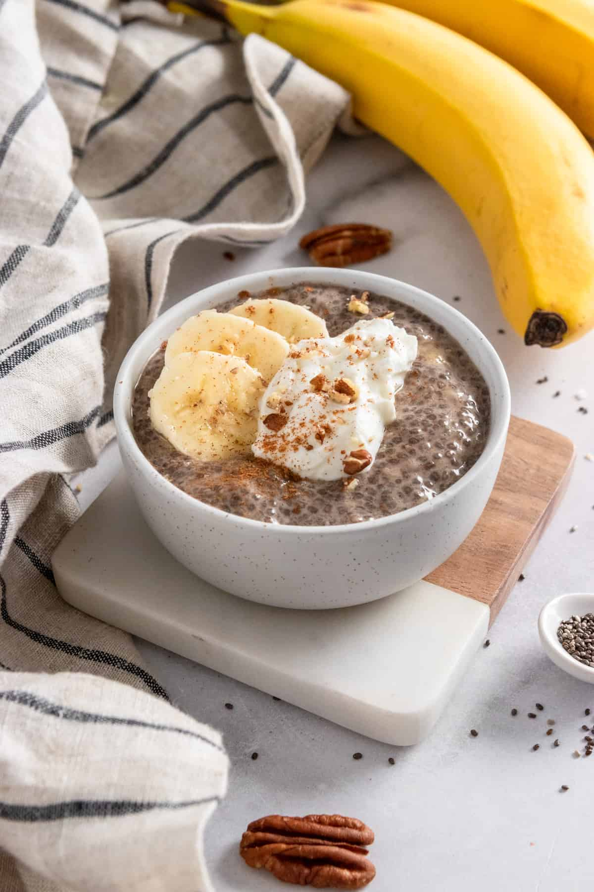 Chia pudding in bowl on coaster with bananas and pecans in the background.