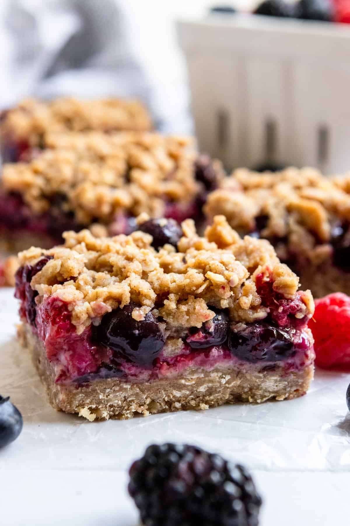 Oatmeal crumble bars on wax paper with berries in white container.