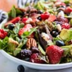 Berries and pecans over green salad.