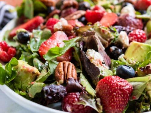 Berries and pecans over green salad.
