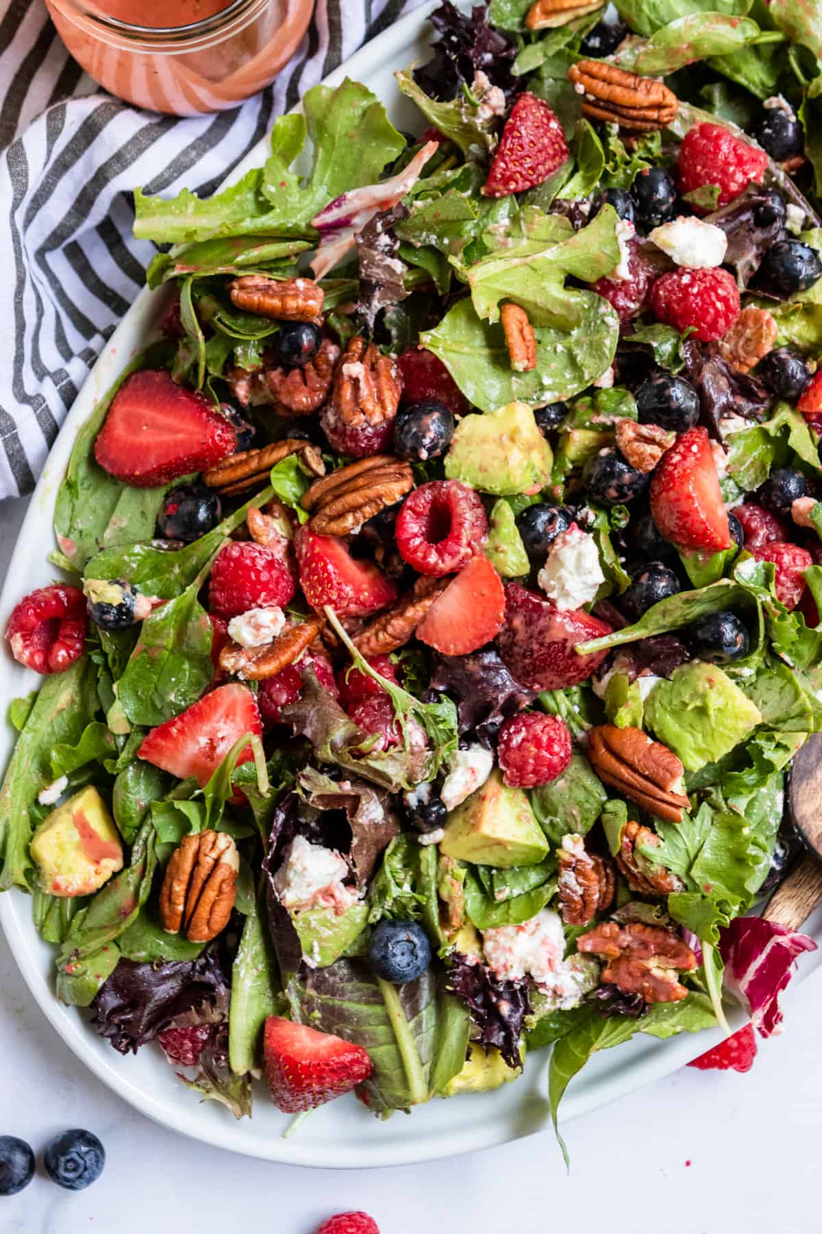 Overhead view of mixed green salad with berries.