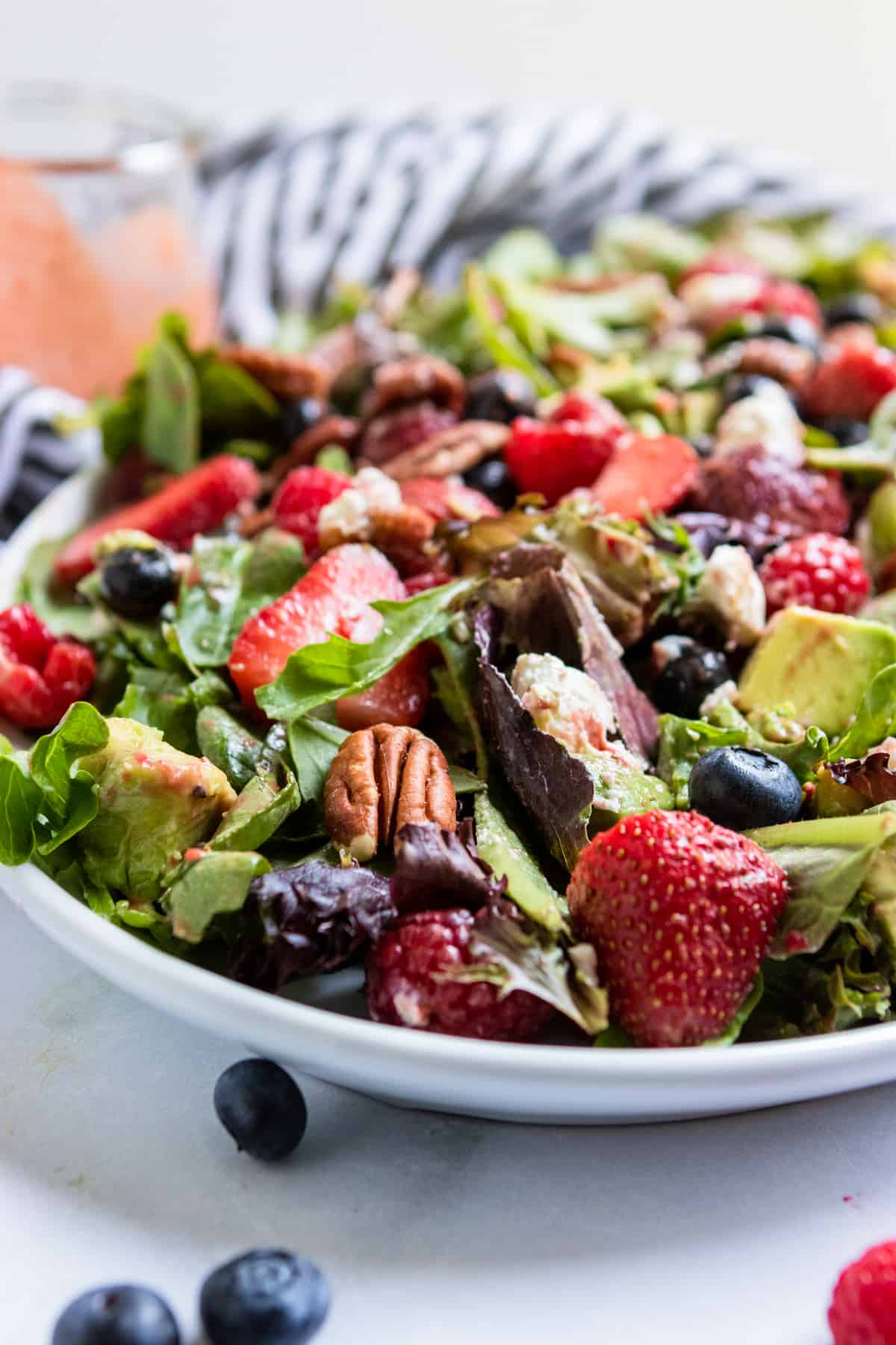 Mixed green salad with berries on white plate with dressing.