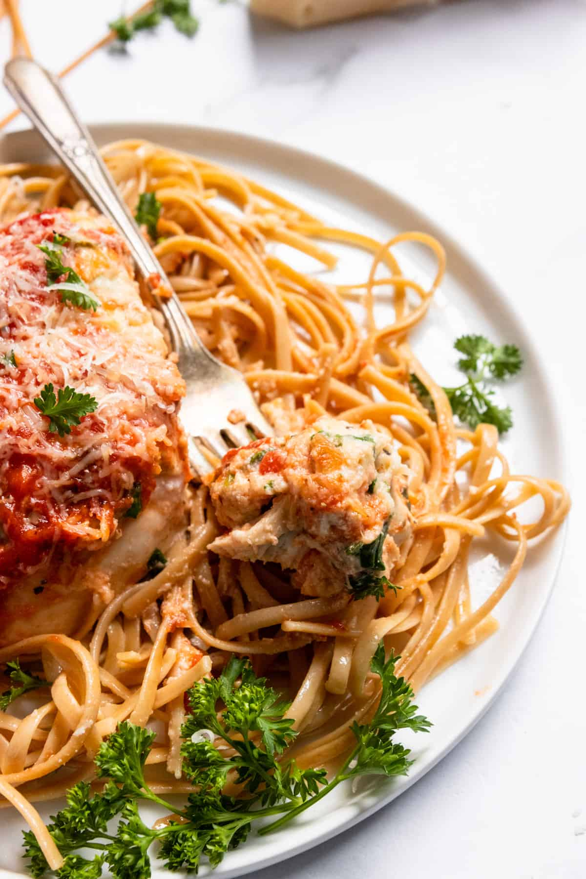 Chicken on fork with ricotta and marinara.
