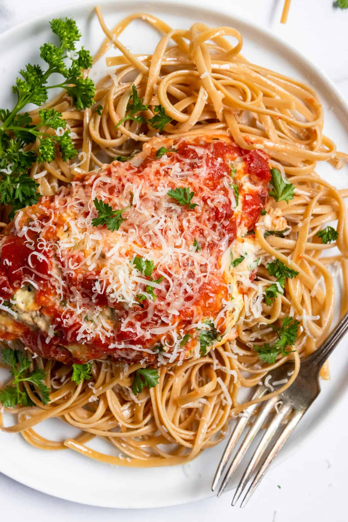 Chicken with marinara and parmesan on pasta with parsley on white plate.