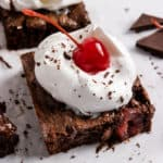 Cherry brownie with whipped cream and cherry.