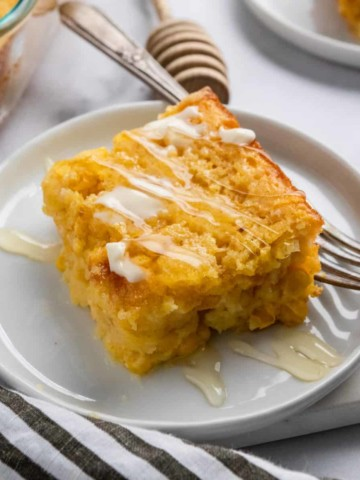 Honey cornbread on plate with butter and honey drizzle.