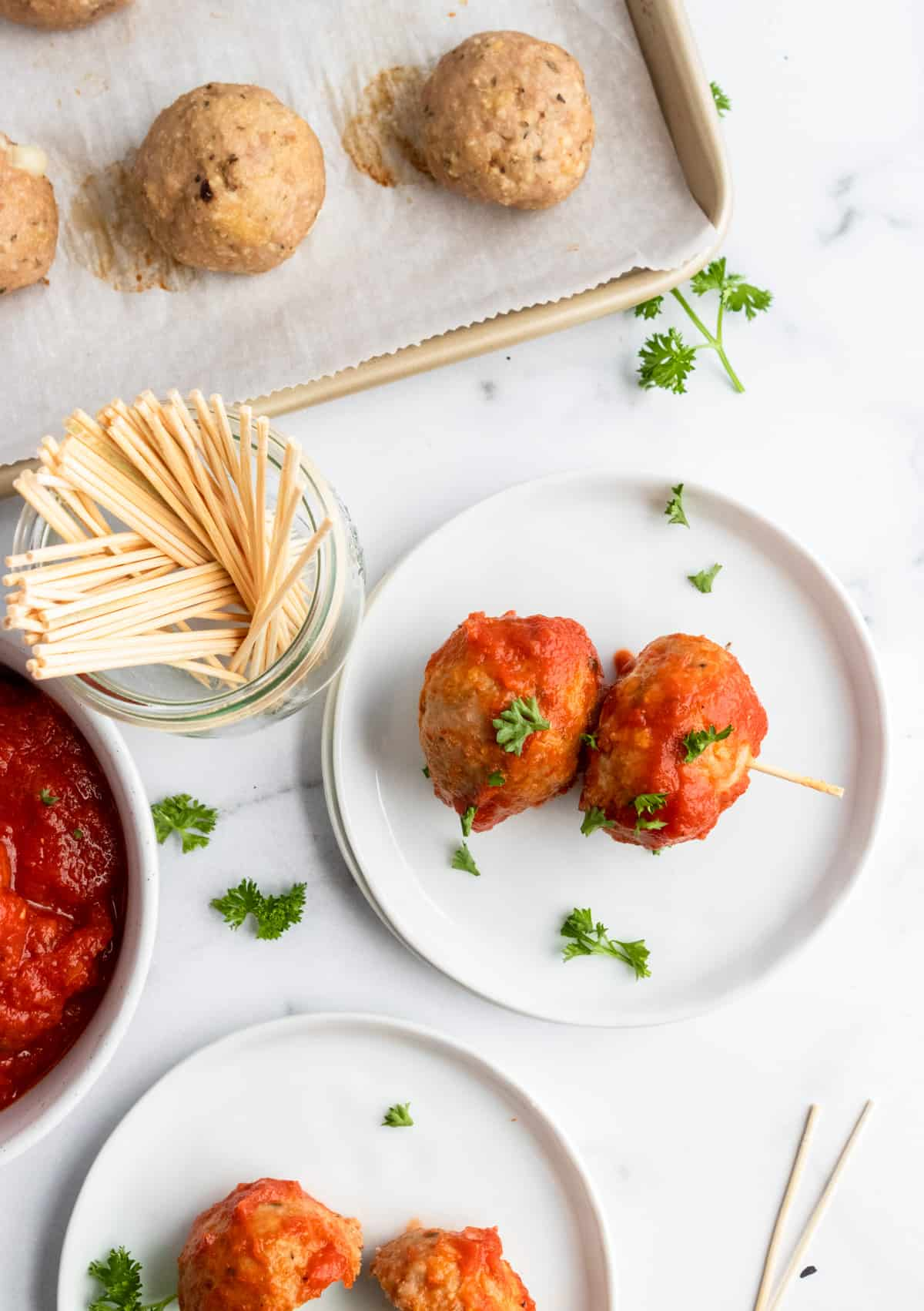 Meatballs on plate with toothpicks.