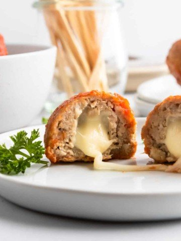Mozzarella stuffed turkey meatballs on plate with cheese stretching.