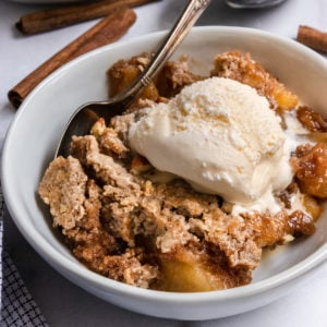 Apple Dump cake in white bowl with ice cream.