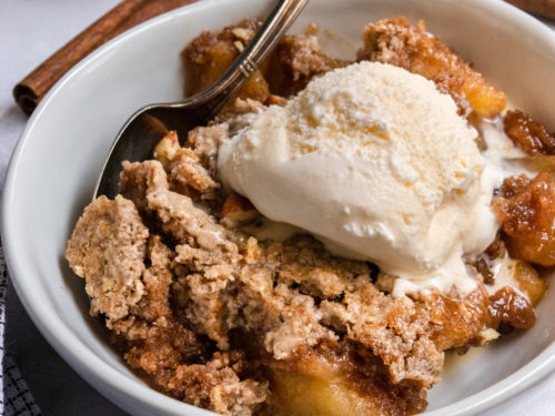 Apple Dump cake in white bowl with ice cream.