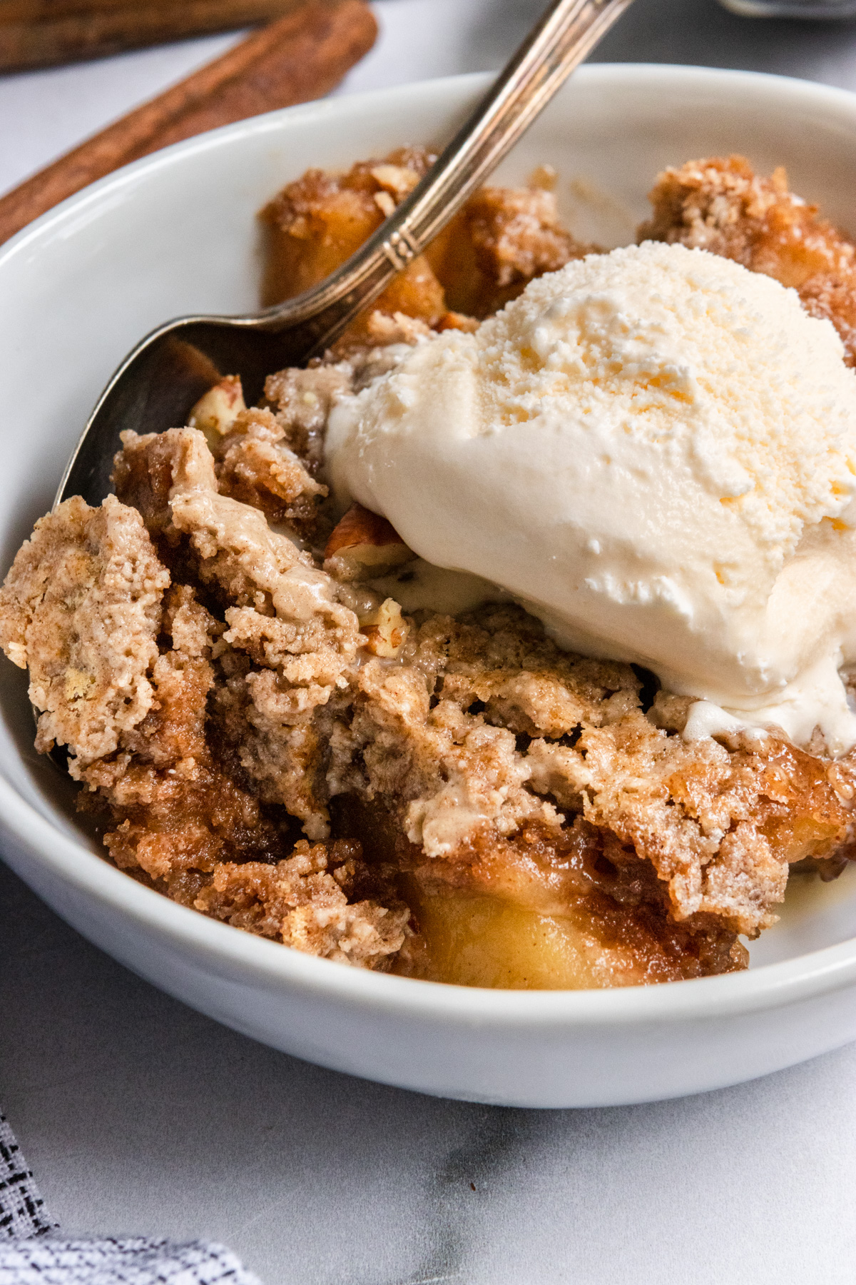 Apple dump cake in bowl with ice cream on top.