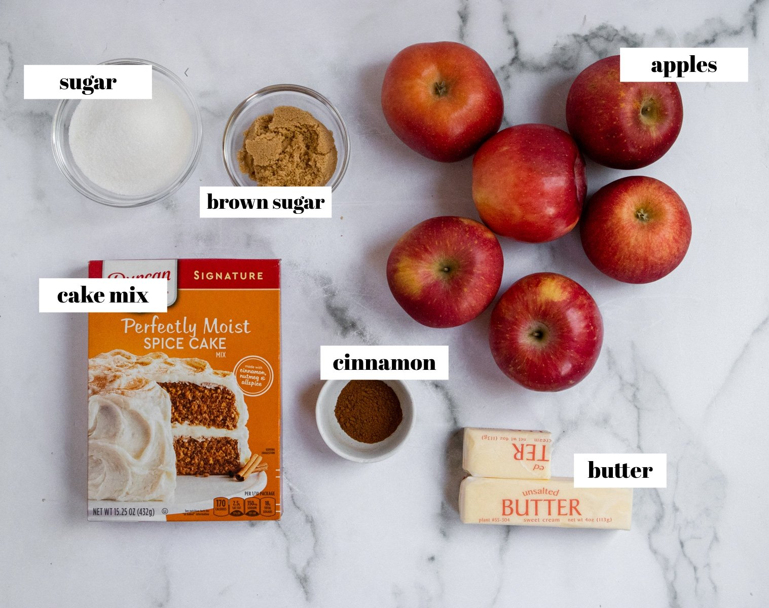 Apples, sugar, cinnamon and ingredients for recipe labeled on counter.