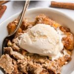 apple dump cake in bowl with ice cream and spoon.