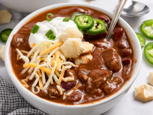 Brisket chili in white bowl with spoon.