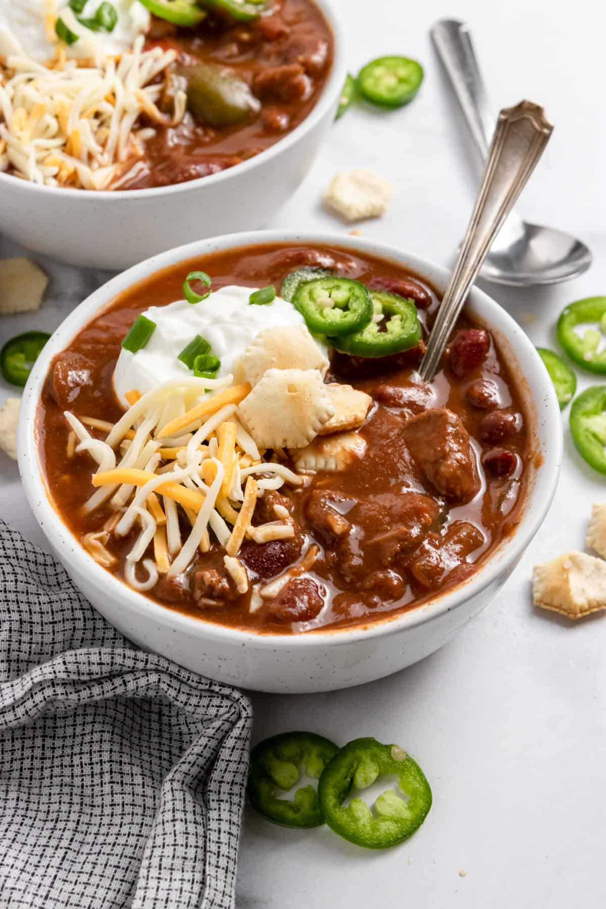 Brisket chili in bowl with sour cream, cheese, crackers and spoon.