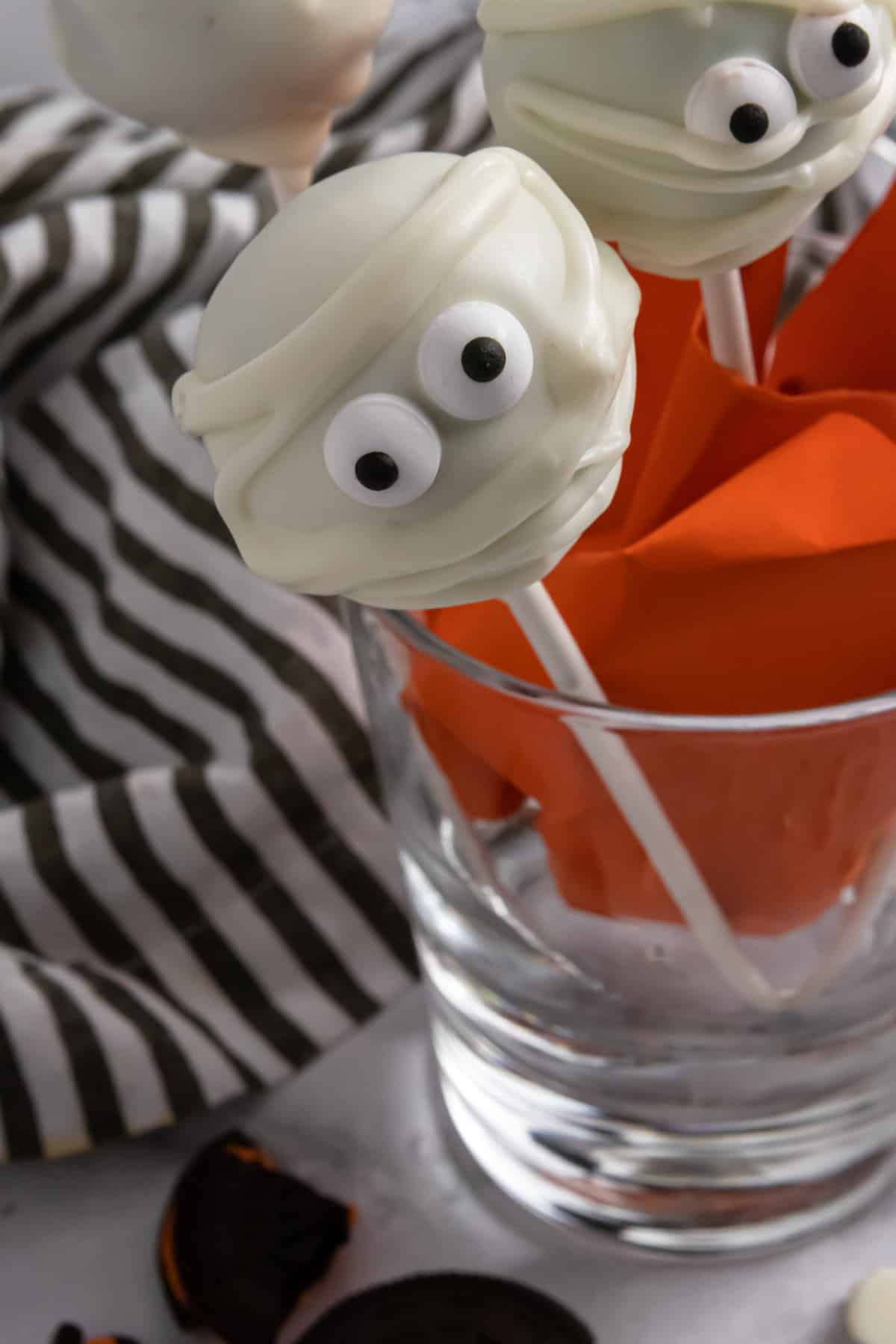 Halloween cake pops in glass cup.
