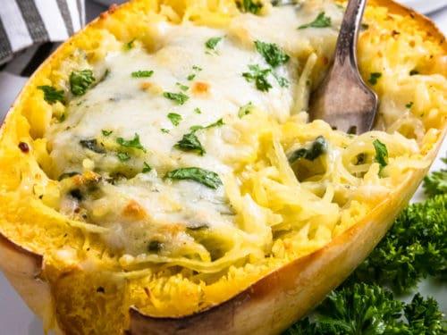 Creamy pesto spaghetti squash half with fork.