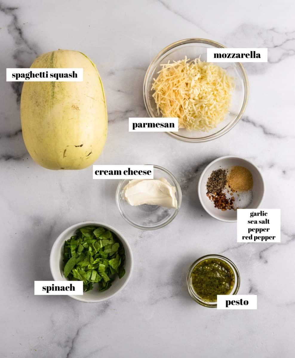Ingredients to make stuffed spaghetti squash labeled on counter.