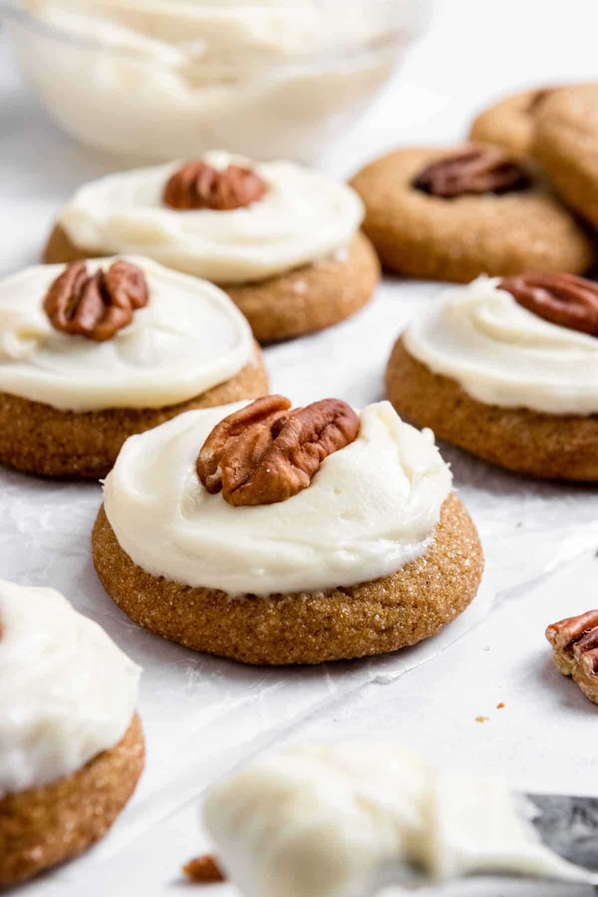 Pumpkin spice cookies with cream cheese icing and pecan on top.