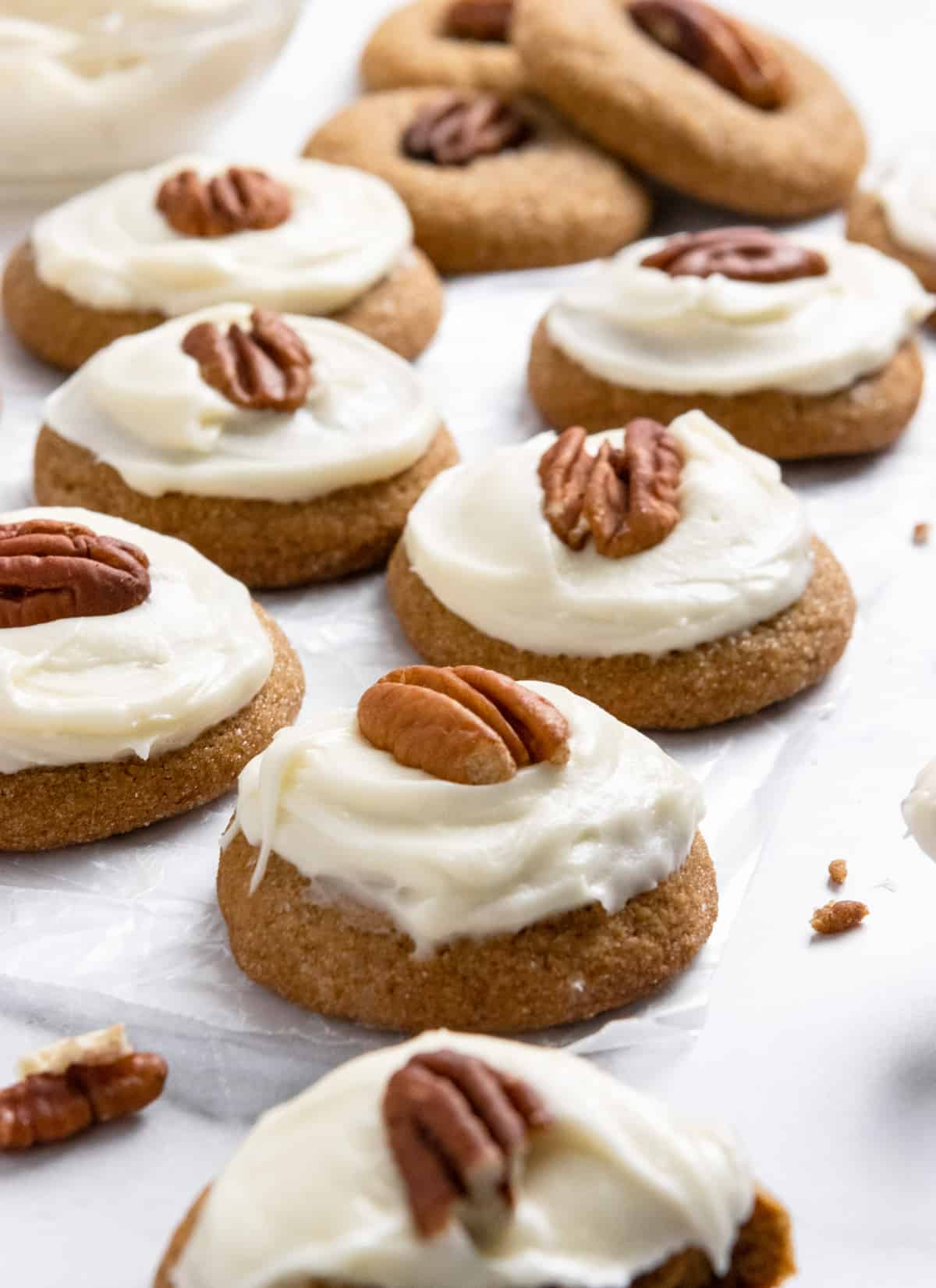 Pumpkin Spice cookies with cream cheese icing and pecan on wax paper.