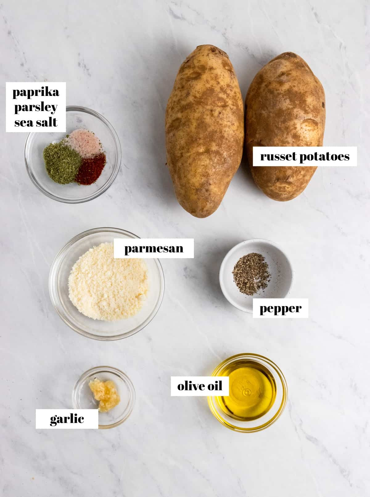 Potatoes, olive oil, parmesan and other ingredients labeled on counter.